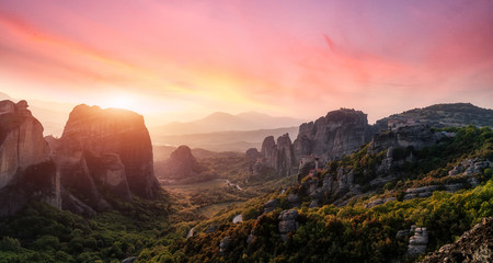 Foto auf Leinwand Rosa hell Fantastic Landscape with monasteries and rock formations in Meteora during sunset, Greece. Mysterious Sunny Morning with colorful sky. Awesome Nature Landscape. Popular travel locations.