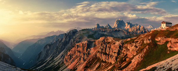 Fotomurales - Wonderful Sunny Landscape of Dolomite Alps during sunrise. Panoramic view of famous Dolomites mountain peaks glowing in beautiful golden evening light at sunset in summer, South Tyrol, Italy.