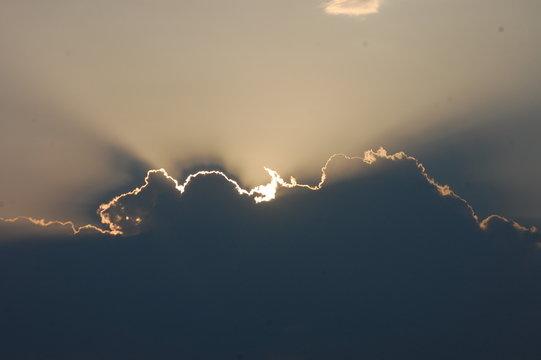 the sun behind the cloud