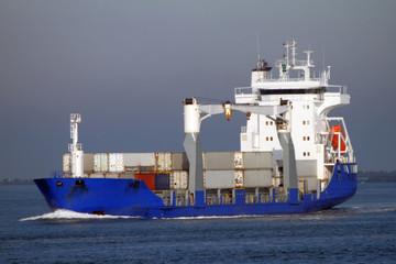 Blaues Feederschiff mit Containern erreicht den Hafen