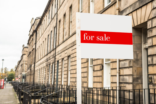 Sign outside an old terraced house on sale in a city centre on a cloudy autumn day. Edinburgh, Scotland, UK.