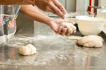 Deurstickers Bakkerij hands crumple dough,