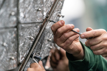 Workers install Waterford Crystal triangles on the Times Square New Year's Eve Ball on the roof of One Times Square in Manhattan