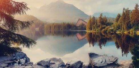 Foto auf Acrylglas Cappuccino Awesome alpine lake during sunset. Stunning Foggy Morning on mountain lake glowing warm sunlight. Unusual Dramatic Scene. Wonderful Autumn Landscape. Beauty in the world. Strbske Pleso Lake.