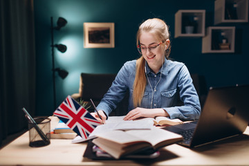 Cheerful young girl in glasses writing during her daily English lesson at home