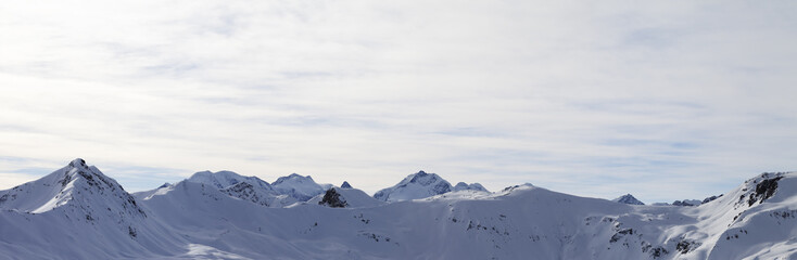 Fototapete - Panorama of high winter mountains with snowy slopes