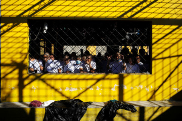 Inmates, members of the MS-13 gang, wait in their cell to be transferred from the Chalatenango penitentiary, in Chalatenango
