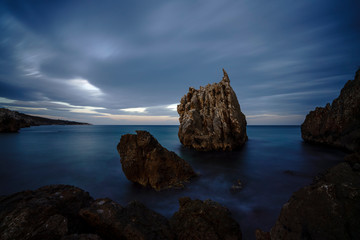 Black sea and the beach with rocks and waves with cloudy sky,