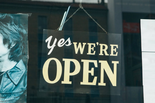 A sign on the glass door of a store or cafe with the inscription Yes we are open