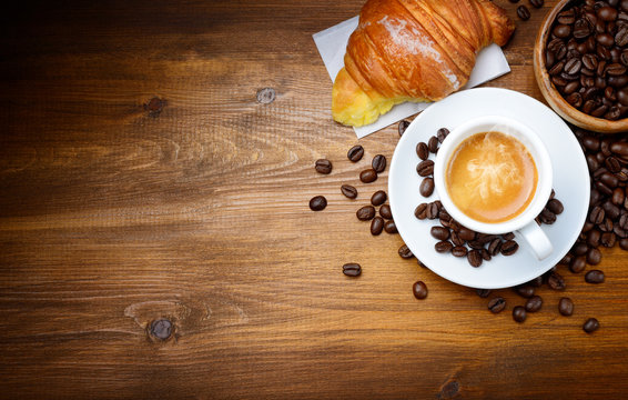 Espresso and croissant with coffee beans on wood background. Top view