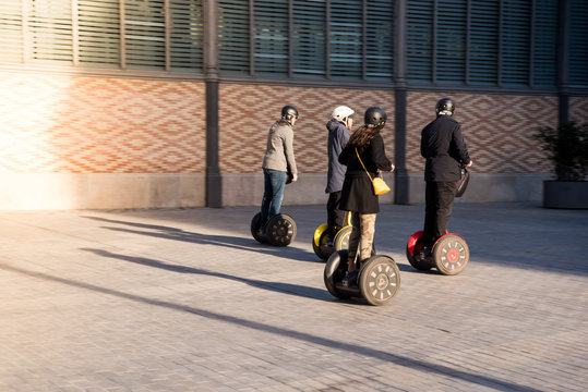 A group of people on eco-friendly Segway scooters on a Spain historic street. Tourists enjoying electric scooters.