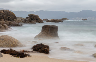 Rocks on the Atlantic coast in northern Spain. The sandy beach with stones is near the town of Quilmas in Galicia. A long exposure with soft waves. The mountainous coastal landscape can be seen in the