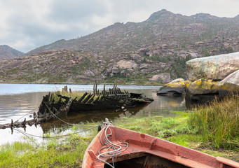 An old broken boat lies in the water at Ezaro. You can see crumbled wood, struts and planks. The river flows through the rocky valley into the Atlantic. It is a foggy winter morning.