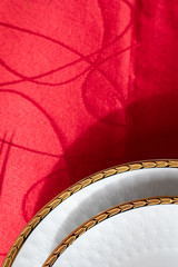 Printed roller blinds Stairs white porcelain dish with golden relief with decorations on a red table. luxury plates and dishes used for celebrations. porcelain plate and setting up the dinner table in red. Christmas party