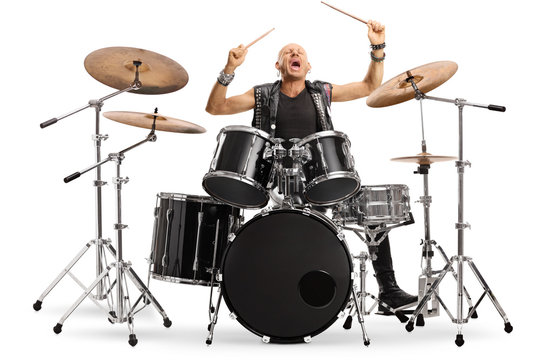Male musician in leather vest playing a drum kit