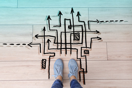 Person standing on floor near arrows pointing in different directions, top view. Concept of choice