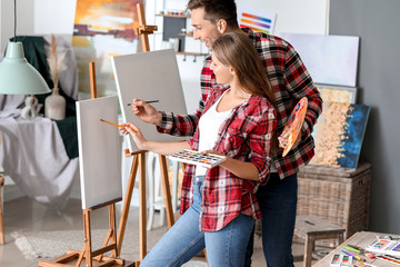 Couple of young artists working in studio