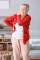 Senior woman suffering from pain in shoulder at home