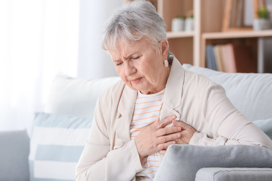Senior woman suffering from heart attack at home
