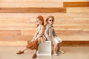 Cute little girls in autumn clothes near wooden wall