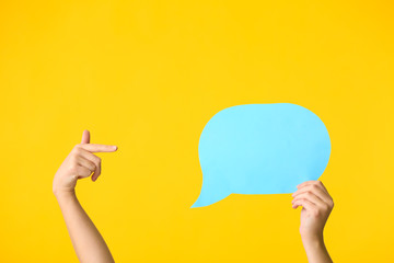 Female hands and blank speech bubble on color background
