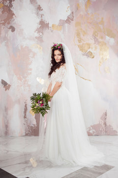 Beautiful young bride in wedding dress with veil on her face