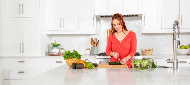 A woman chops vegetables in a modern farmhouse kitchen.