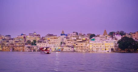 Wall Mural - Udaipur Lal ghat, houses and City Palace on bank of lake Pichola with water riffles - Rajput architecture of Mewar dynasty rulers of Rajasthan. Sunset at Udaipur, India. Horizontal panning