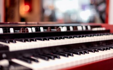 A double manual vintage organ keyboard with tone stops in shallow depth of field.