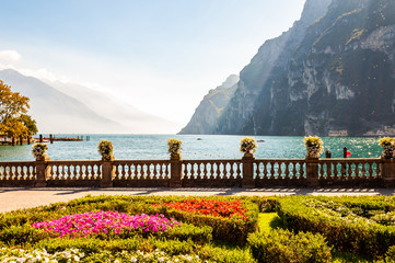 Garda lake promenade with colorful flowerbeds with growing and blooming plants, classic stone fence...