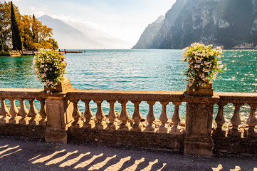 Beautiful Garda lake promenade with classic stone fence railings built on the edge with flowerpots...