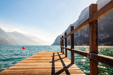 Scenic view on wooden planks pier with railings built on northern shore of beautiful Garda lake in Lombardy, Italy surrounded by high dolomite mountains and crystal clear blue water of the lake. Riva