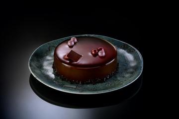 Torta ai 3 cioccolati con piatto su piano nero lucido
