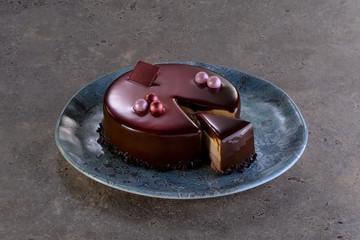 Torta ai 3 cioccolati con glassa lucida con porzione affettata