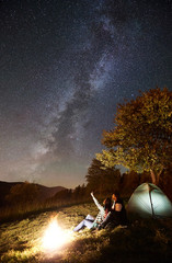 Keuken foto achterwand Chocoladebruin Young couple travelers resting at bonfire beside camp and tourist tent. Woman pointing at amazing night sky full of stars and Milky way. On the background beautiful starry sky, mountains and big tree