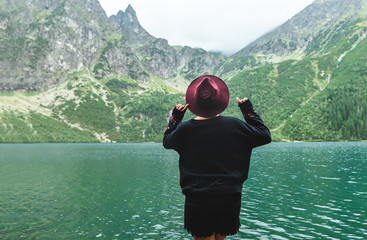 Back of a stylish girl in dark clothing on a background of a mountain lake with blue water and mountains with clouds. Background. Hipster tourist woman on the shores of Lake Morskie Oko