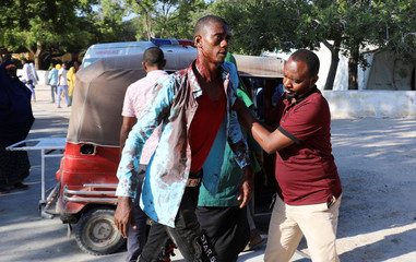 A man assists a civilian injured at the scene of a car bomb explosion at a checkpoint in Mogadishu