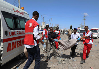 Civilians carry the dead body of a man killed in a car bomb explosion at a checkpoint in Mogadishu