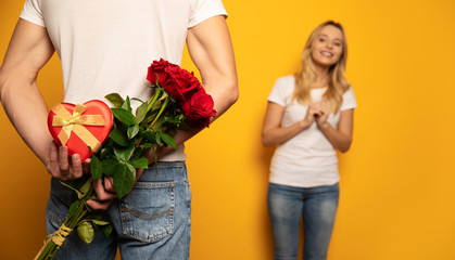 Roses for my dear. Enchanting woman in a casual outfit is holding her hands together impatiently,...