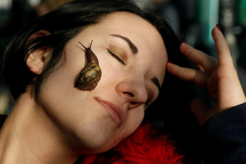 A woman poses for a picture with a snail crawling on her face at a snail farm in Stavropol region