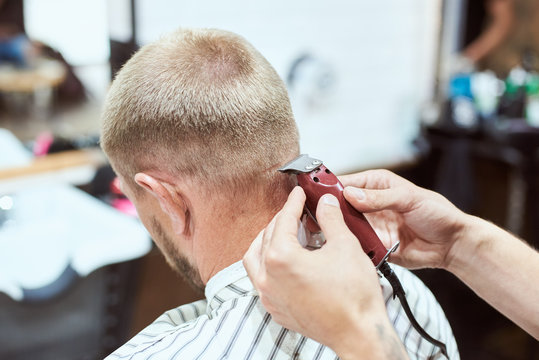 Dark blonde man at barber shop is having his nape shaved with a trimmer, hairdresser is holding a red tool, stripe cape on