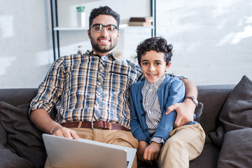 smiling jewish father with laptop and son looking at camera in apartment
