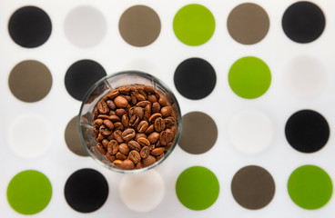 Composition with glass of coffee beans on coloured dots mat