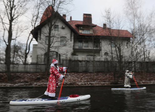 People dressed as Father Frost paddle on stand-up boards along a canal in central Saint Petersburg