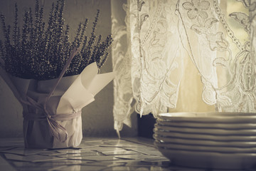 Composition on a windowsill in a restaurant with a stack of white plates and heather flowers in a basket decorated with thin paper.