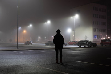 Woman stands alone at parking lot. City landscape at foggy night. Long exposure. Light trails. Fotomurales