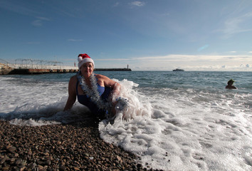 A woman wearing a Santa Claus hat poses for a picture on a beach during a parade to celebrate the upcoming Christmas and New Year in Yalta