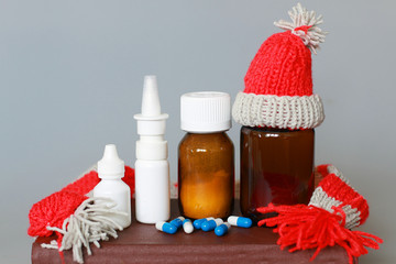 nose drops, nasal spray, cough syrup in a cap and scarf on a brown background