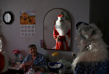 Volunteers dressed as Father Frost and Snow Maiden present a gift to a resident of a nursing home on the occasion of the Christmas and New Year holidays in Omsk region
