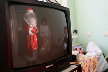Volunteers present a gift to a resident of a nursing home on the occasion of the Christmas and New Year holidays in Omsk region